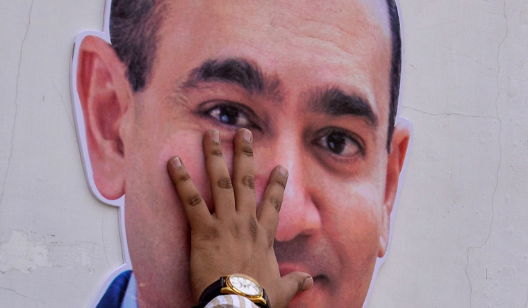 A Congress supporter puts his hand on the face of a cut-out of billionaire jeweller Nirav Modi during a protest in New Delhi | AFP