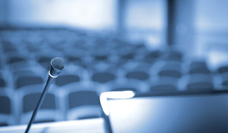 conference-hall-empty-mic-chairs-shutterstock
