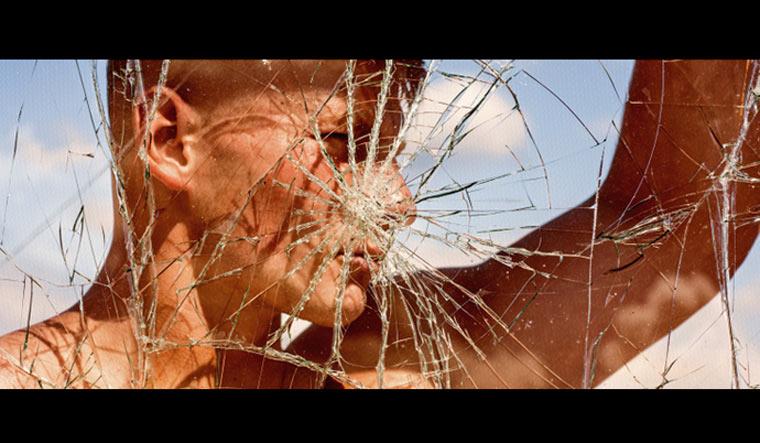 Strong-man-seen-through-cracked-glass-revenge-jealousy-vengeance-ambition-muscular-strength-shut
