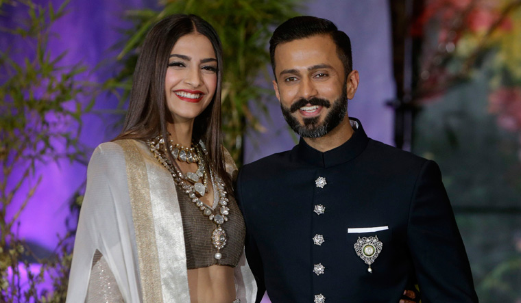 Bollywood actress Sonam Kapoor left and her husband Anand Ahuja pose for