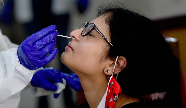 A medic collects a sample of a woman for COVID-19 test at NDMC Child welfare centre, in Sarojini Nagar, New Delhi | PTI