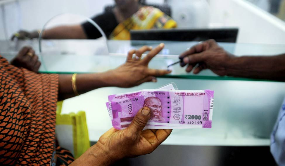 A woman holds Rs 2,000 notes as she has her finger marked with indelible ink after exchanging 500 and 1000 INR banknotes at a bank in Chennai