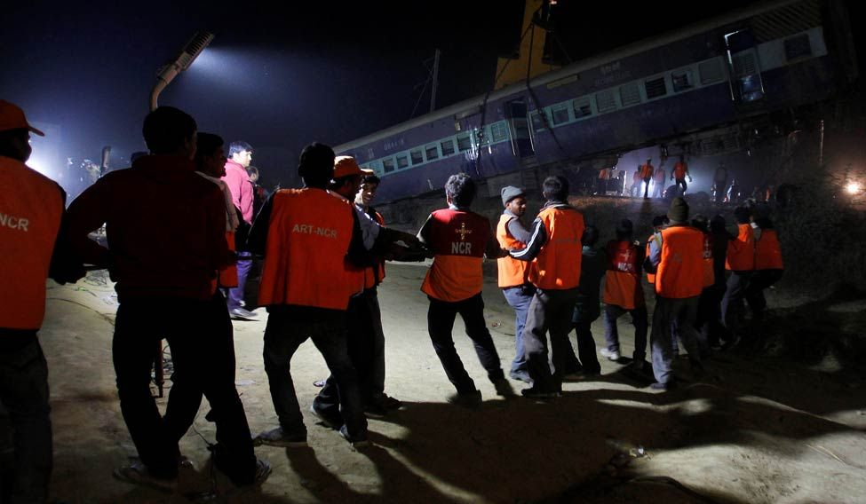 Rescue workers move a carriage at the site of the train derailment in Pukhrayan near Kanpur