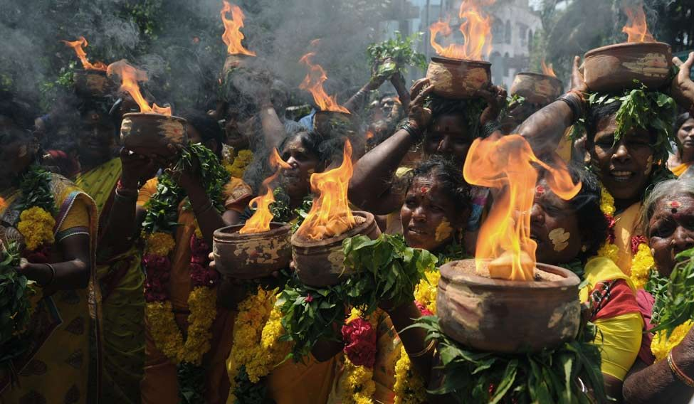 AIADMK women members carry burning pots during a ritual offered for the health of Jayalalithaa near Apollo hospital in Chennai