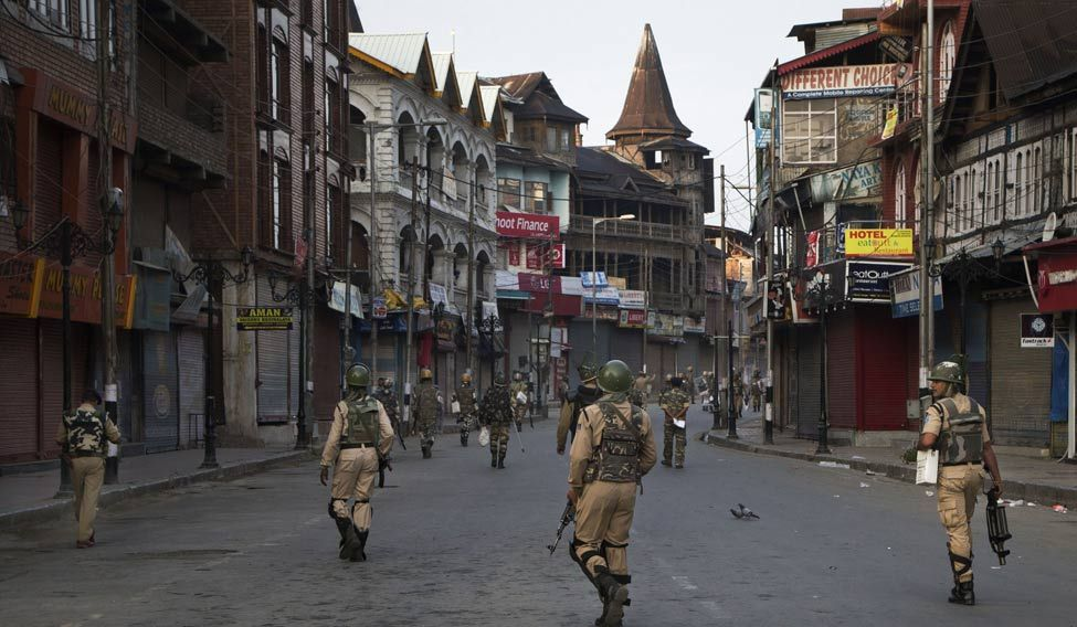 Paramilitary soldiers patrol a deserted street during curfew in Srinagar