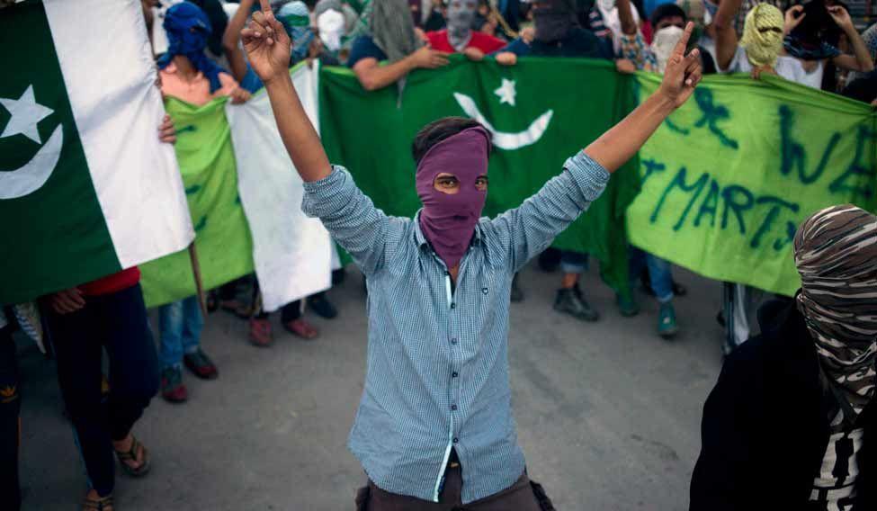 A masked Kashmiri protester shouts freedom slogans in Srinagar