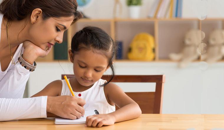 handwriting-child-school-Indian-woman-helping-her-daughter-with-homework-shut
