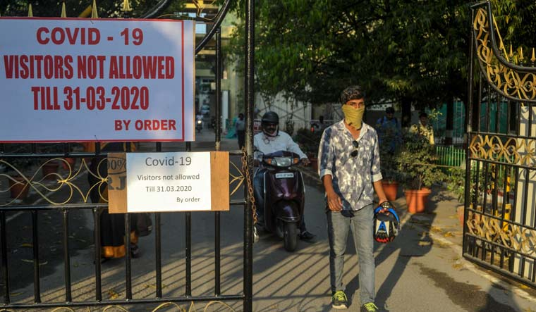 A man wearing a facemask amid concerns over the spread of COVID-19 comes out from a government office as the sign board displayed at the entrance forbids visitors, in Hyderabad | AFP