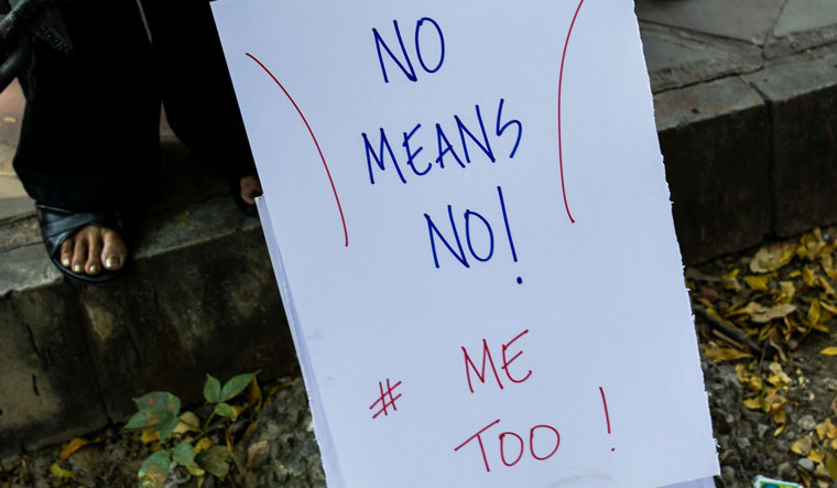 A journalist holds a placard at a protest against sexual harassment in the media industry in New Delhi on Saturday | AFP