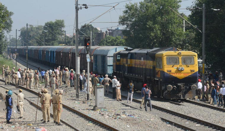 Punjab Police personnel stand guard as a freight train passes along rail tracks towards Amritsar railway station | AFP