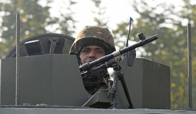 An Indian army soldier looks on from an armoured vehicle after a gun battle between suspected militants and Indian security forces in the Nowgam area | AFP