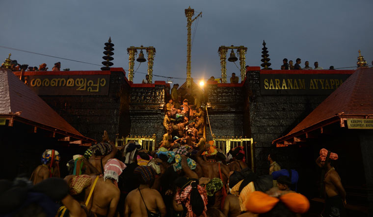 Devotees climb over the holy eighteen golden steps to worship Lord Ayyappa at Sabarimala temple | AFP