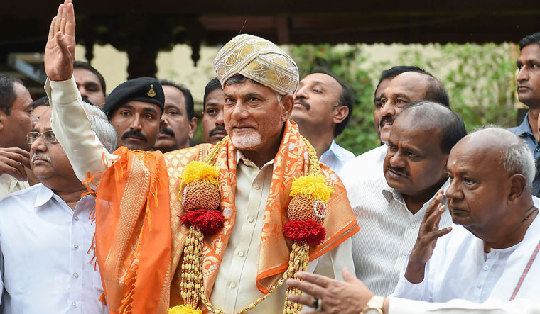 Andhra Pradesh Chief Minister N. Chandrababu Naidu waves after being felicitated by Karnataka Chief Minister H.D. Kumaraswamy and former prime minister H.D. Deve Gowda ahead of a meeting, in Bengaluru | PTI