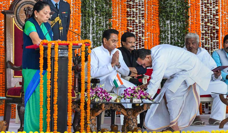 Minister Hukum Singh Karada seeks blessing from Chief Minister Kamal Nath during a swearing-in ceremony at Raj Bhawan, in Bhopal | PTI