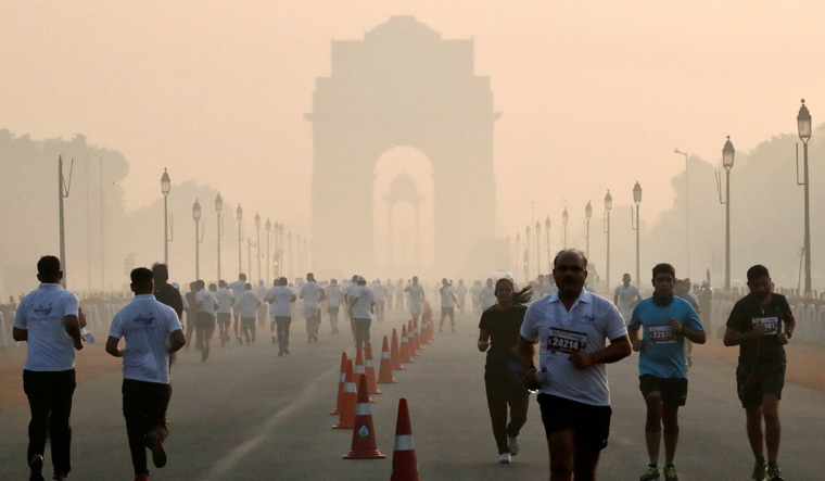 [File] Participants run during a half marathon organised by Indian National Security Guard (NSG) on a smoggy morning in New Delhi on November 18 | PTI