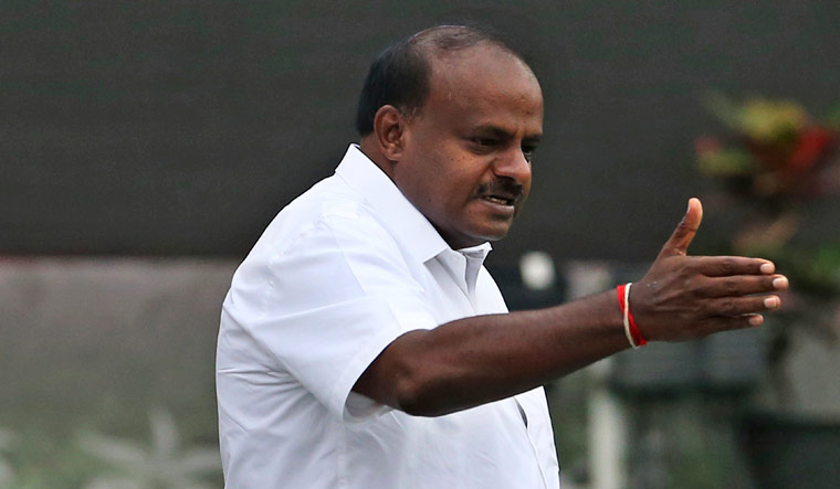 H. D. Kumaraswamy gestures to the gathering as he arrives to be sworn in as Chief Minister of Karnataka, in Bengaluru on Wednesday | AP