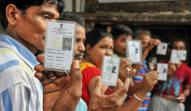 Voters show their Election Commission cards as they queue to cast their vote at a polling station during Maheshtala Assembly by-election in South 24 Parganas district of West Bengal, on Monday | PTI