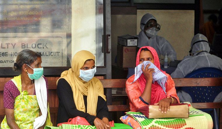 [File] People wear masks as they wait outside a casualty ward at a hospital in Kozhikode | Reuters