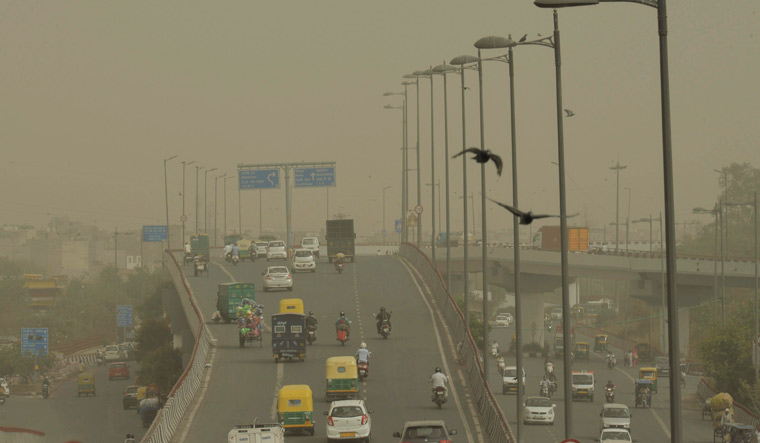 Vehicles ply slowly on a road as dust envelopes the sky over New Delhi, on Wednesday | PTI