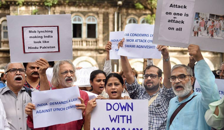 [FILE] Documentary filmmaker Anand Patwardhan with other activists raise slogans to condemn mob lynching, in Mumbai | PTI
