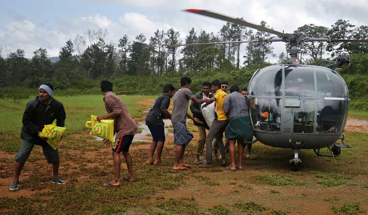 People unload food and relief material from an Air force helicopter at Nelliyampathy Village | Reuters