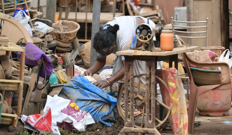 A woman inspects the belongings at her house affected by flood at Aluva in Kochi | Josekutty Panackal