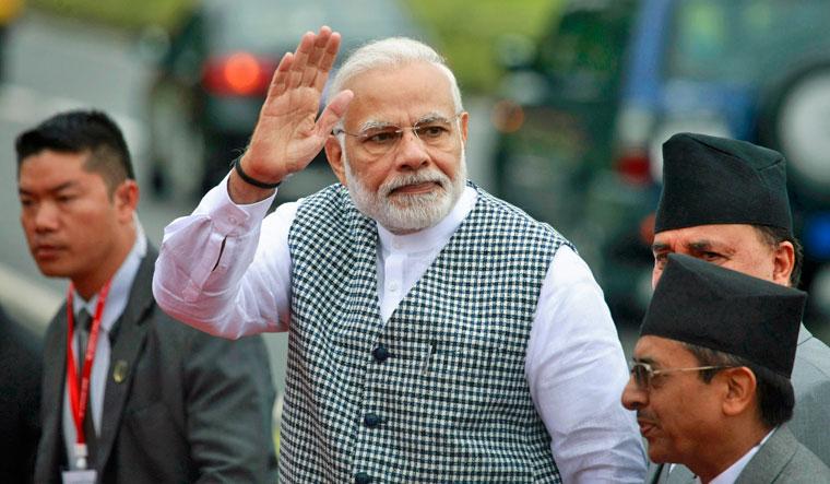 Prime Minister Narendra Modi waves to the media upon arrival at Tribhuvan International Airport in Kathmandu, Nepal, Thursday