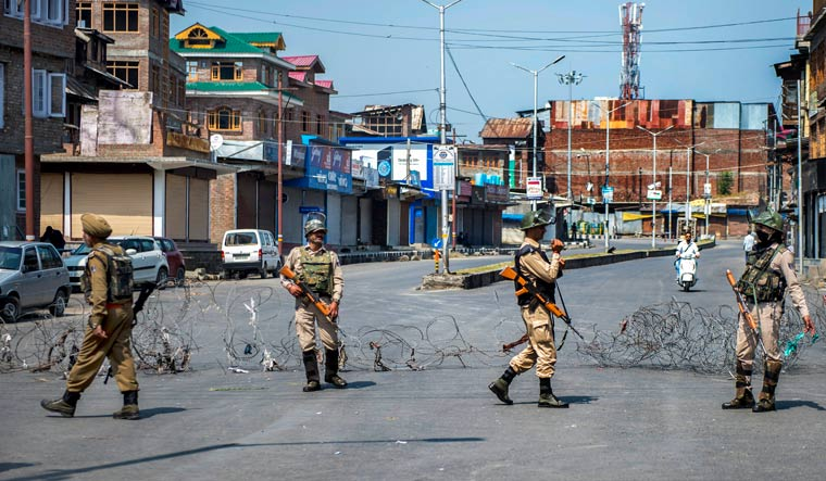 Security personnel stand guard along a barbed wire during a strike called by separatist leaders, in Srinagar | PTI