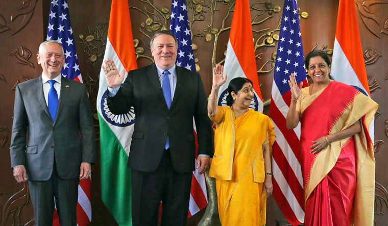 From left, U.S. Defense Secretary James Mattis, U.S. Secretary of State Mike Pompeo, Indian Foreign Minister Sushma Swaraj and Indian Defense Minister Nirmala Sitharaman raise their hands before a meeting in New Delhi, India, Thursday