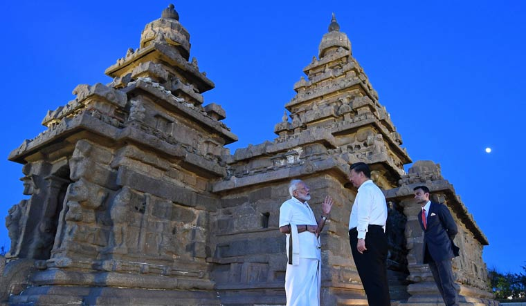 Prime Minister Narendra Modi talks with Chinese President Xi Jinping during their visit to the Shore Temple monuments in Mamallapuram | AFP