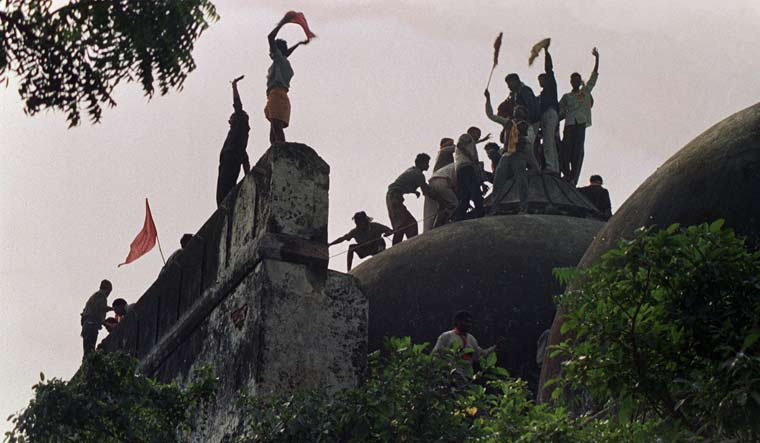 [File] Right wing activists wave banners as they stand on the top of a stone wall and celebrate the destruction of the Babri Mosque in Ayodhya on December 6, 1992 | AFP