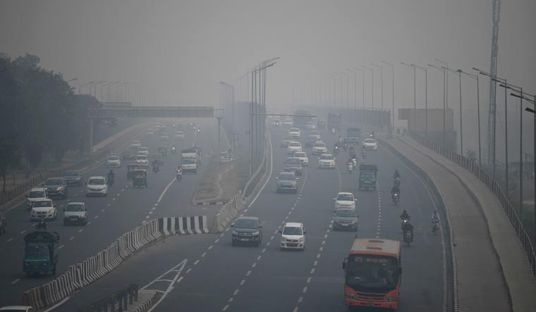 Commuters drive along a motorway under heavy smog conditions in New Delhi | AFP