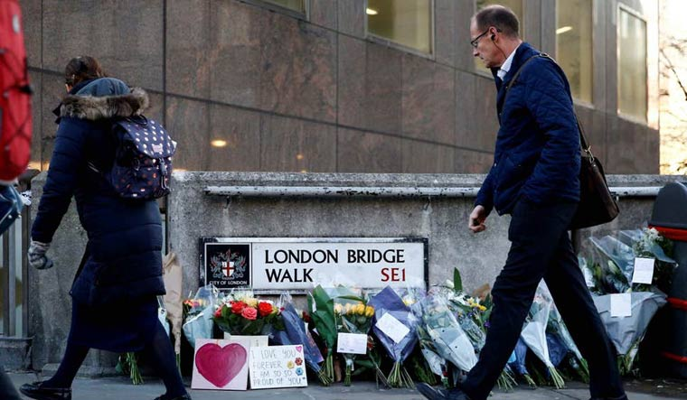 [File] A commuter looks at flowers and signs left at the scene of the attack on London Bridge | Reuters
