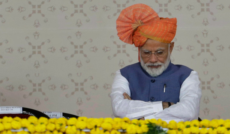 Prime Minister Narendra Modi sits during the launch of national pension scheme for unorganised workers in Ahmadabad | AP