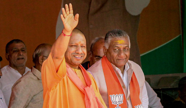 Uttar Pradesh Chief Minister Yogi Adityanath waves at party workers at an election rally in support of BJP candidate V.K. Singh (R) in Ghaziabad | PTI