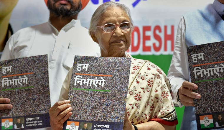 Delhi Pradesh Congress Committee president Sheila Dikshit displays a copy of party's manifesto for the upcoming Lok Sabha elections at a press conference at DPCC office in New Delhi | PTI