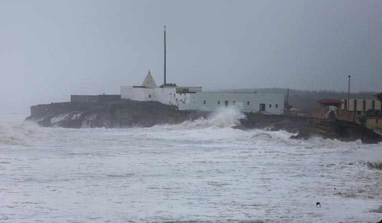 A huge wave hits the wall of a temple along the sea shore during high tide, at Veraval | PTI