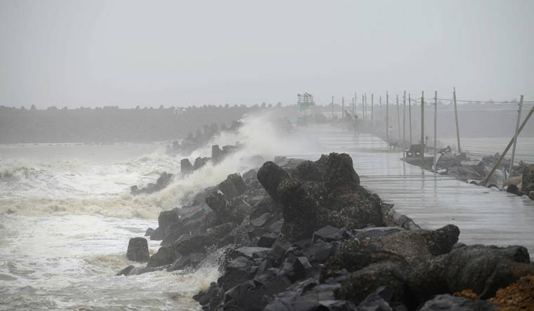 [File] People stand on a breakwater as waves near Bhidiya fishing colony in Gujarat's Veraval | AFP