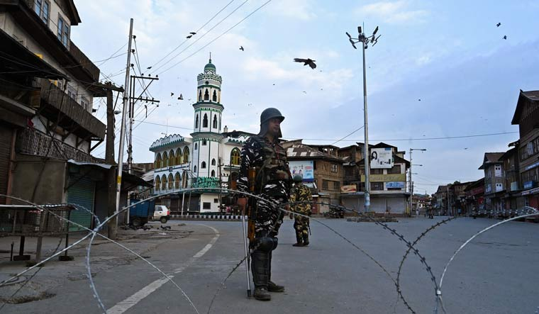Security personnel stand guard on a street during a lockdown in Srinagar | AFP