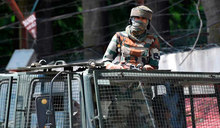 An Army soldier stands alert in a truck while travelling in a convoy in Srinagar   AFP