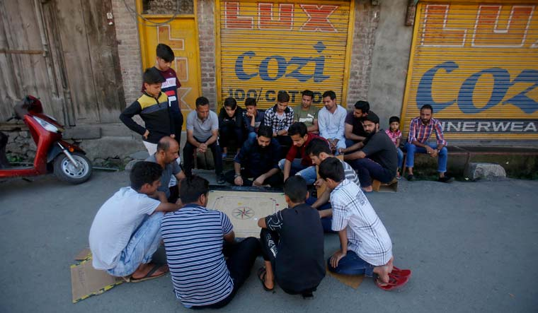 Kashmiri men play a board game at a closed market during security restrictions in Srinagar | AP