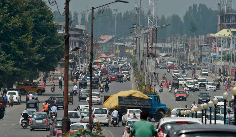 Residents drive along a busy road in Srinagar | AFP