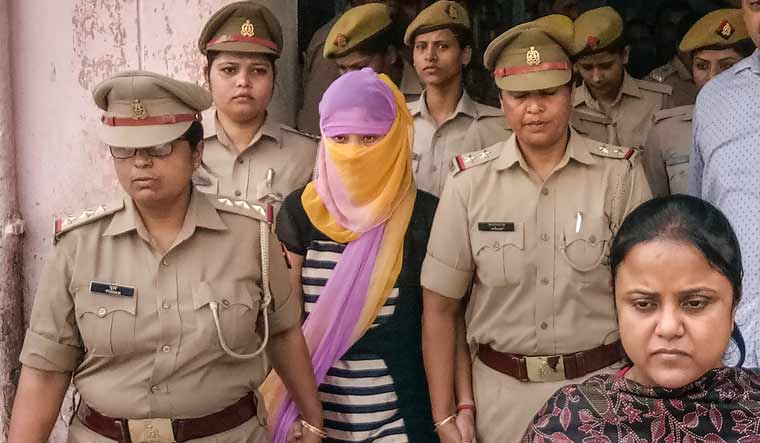 The woman law student (face covered), who alleged BJP leader Chinmayanand of sexual misconduct and harassment, is seen outside a government hospital after a medical examination, in Shahjahanpur | PTI