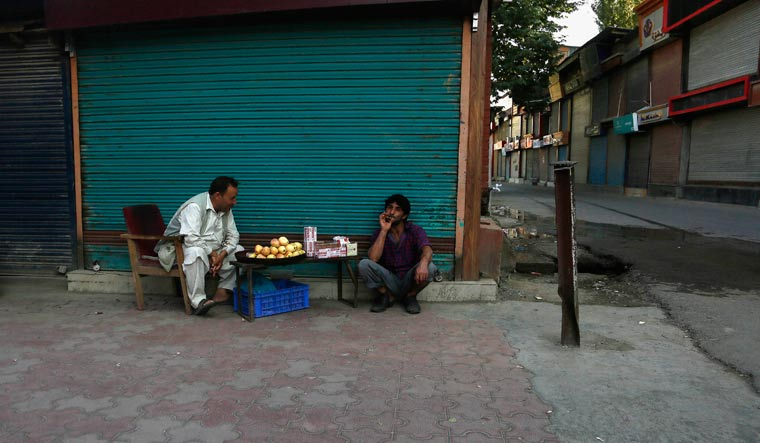 A Kashmiri man sitting near a street vendor at a closed market in Srinagar | AP