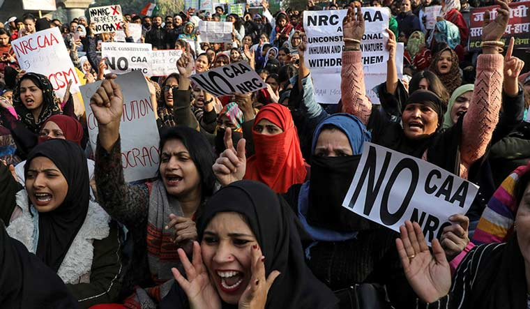 Demonstrators carry posters during a protest against a new citizenship law, outside the Jamia Millia Islamia University in New Delhi | Reuters