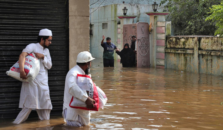 People wade through a flooded street after heavy rainfall at Baba Nagar in Hyderabad | AP