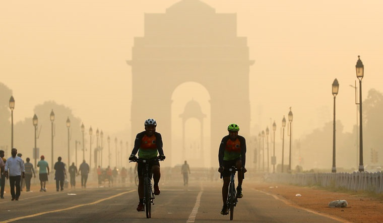 Men ride their bicycles in front of the India Gate shrouded in smog, in New Delhi | Reuters