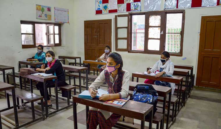 Students wearing face masks attend a class at a school that was reopened after closure for months owing to coronavirus pandemic, in Amritsar,