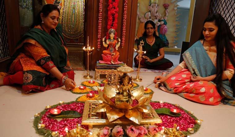 Women light earthen lamps on a rangoli, a hand decorated pattern on the floor, as part of Diwali festivities | AP