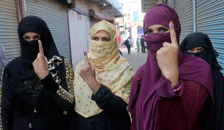 Women show their fingers marked with indelible ink after casting vote during the Madhya Pradesh Assembly bypolls in Raisen district | PTI